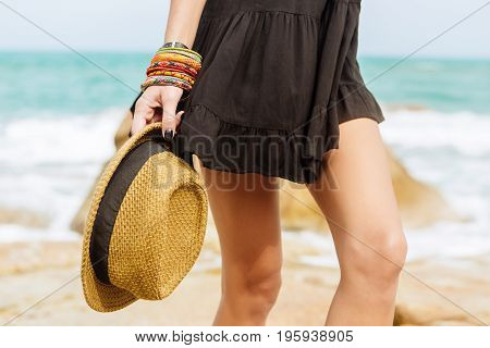 Sexy lady in sunglasses and little black summer dress flying in the wind hold her summer straw cap. Beauty cute girl on a tropical beach sea ocean shore with large stones. Outdoor summer lifestyle.