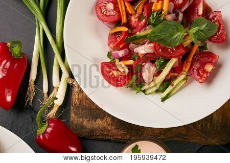 Fresh summer low-calories vegetable salad with tomatoes cucumbers carrots onions fresh bell peppers and garlic on wooden board over the dark stone background. Heathy vegetarian food and detox concept