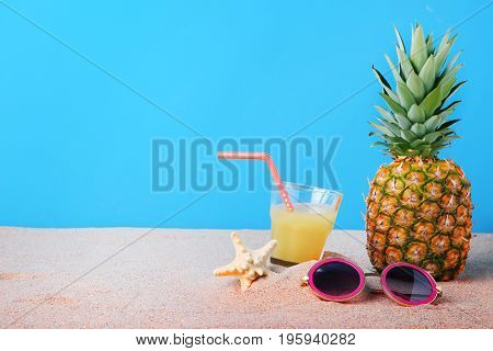Pink Sunglasses With Glass Of Juice And Pineapple On The Beach Sand
