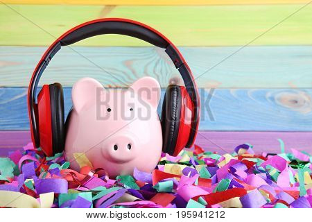 Headphones on piggybank on the colourful confetti