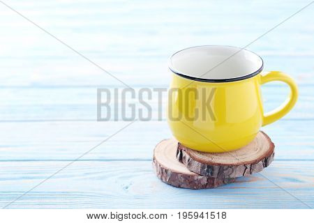 Yellow mug on the blue wooden table