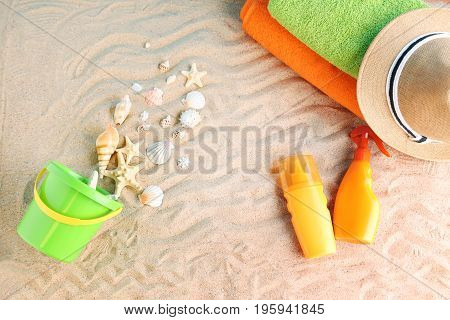 Green bucket with seashells and beach accessories on beach sand