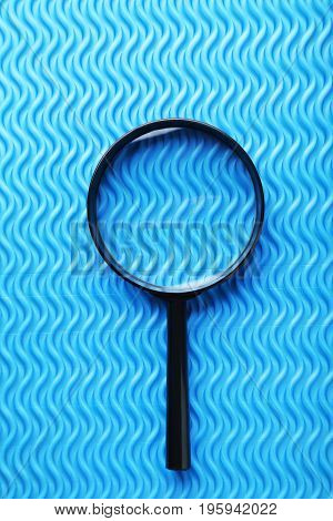 Black magnifying glass on the blue background