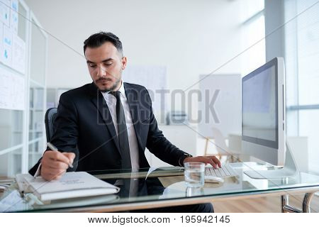 Serious businessman writing on folder with files