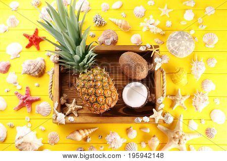 Wooden tray with pineapple and coconuts on yellow wooden table