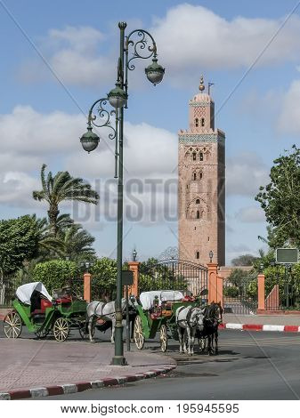 Koutoubia mosque in Marrakech, Morocco  with horse-drawn carriages in front