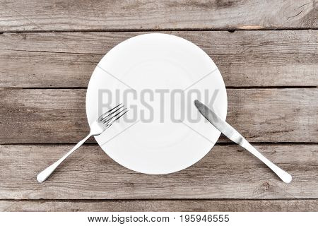 Top View Of Arranged Empty Plate, Fork And Knife On Wooden Table