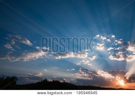 Sunset sky with sun beams bursting through the dark clouds. Conceptual meditation background. Hope, prayer, God's mercy and grace