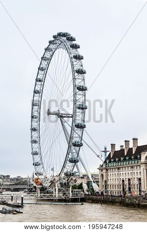 The London Eye along the Thames River on a Cloudy Day