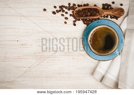 Coffee cup spoon with beans and tablecloth on wooden table