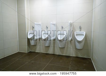 modern restroom interior with white urinal row