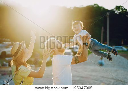 Beautiful red-haired woman with her husband and a wonderful son walking on a summer beach