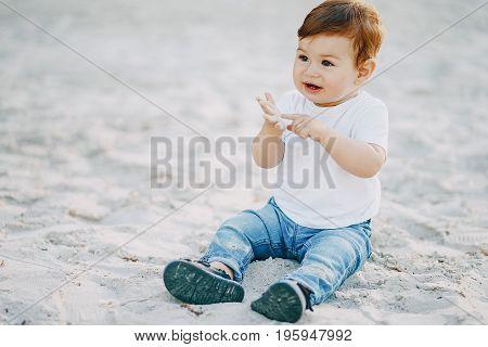 Little cute boy sits on a summer beach on the sand