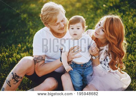 Beautiful red-haired woman with her husband and a wonderful son on a summer park