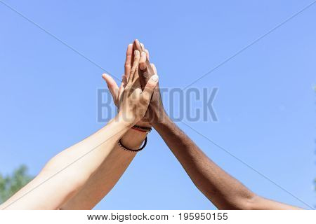 cropped shot of friends giving high five to each other against blue sky