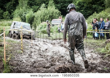 LUBOTIN UKRAINE - JULY 23 2016: RFC Ukraine Wild Boar Challenge 2016. One of the participants of the race walking through the deep mud.