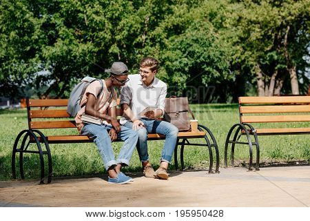 Multicultural Young Students Sitting On Bench And Studying In Park Together