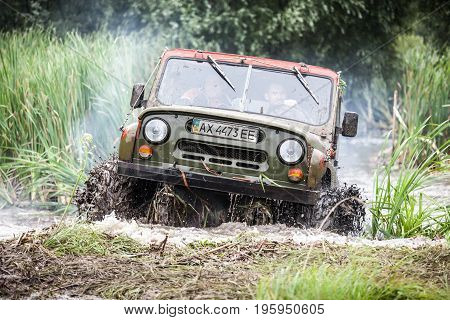 LUBOTIN UKRAINE - JULY 23 2016: RFC Ukraine Wild Boar Challenge 2016. Custom built Off-road Trophy UAZ 469 leaves the swamp at high speed.