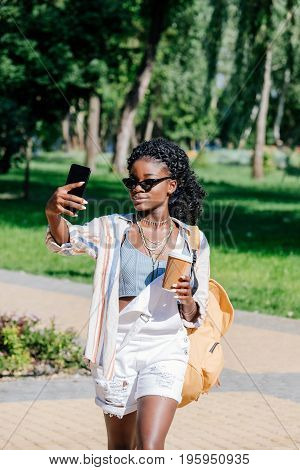 African American Woman With Coffee To Go In Hand Taking Selfie On Smartphone