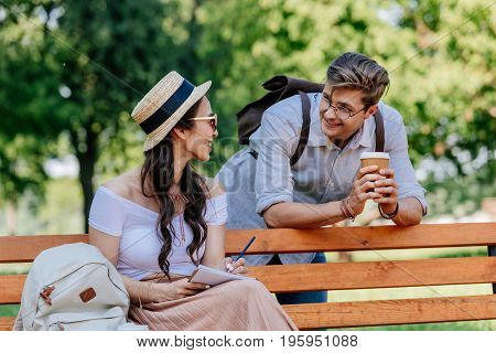 Smiling Multicultural Couple Having Conversation While Sitting On Bench In Park