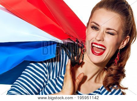 Shopping. The French way. Portrait of happy stylish fashion-monger with shopping bags of the colours of the French flag isolated on white background winking