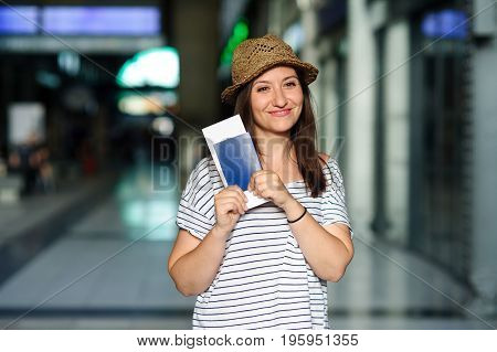 Cheerful tourist with the passport and tickets. Summer holiday. Railway station.