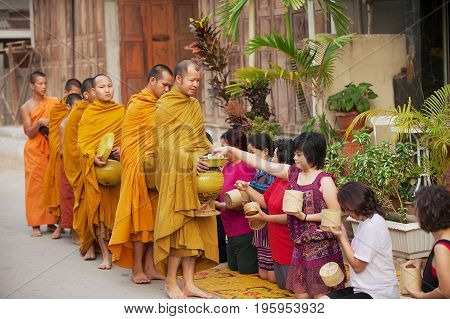 CHIANG KHAN, THAILAND - APRIL 18, 2010: Unidentified people offer sticky rice to Buddhist monks in the morning in Chiang Khan, Thailand.