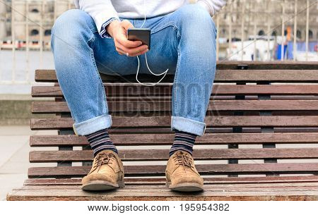 Hipster guy sitting on bench with turn up jeans and brown chamois shoes holding smartphone with headphones. Young man listening music and typing message on the mobile phone during a travel in London.