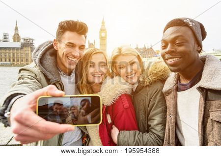 Group of multiracial happy friends taking a selfie with Westminster Palace at the background with Big Ben Tower in London. Traveling concept of happiness and multi ethnic people.
