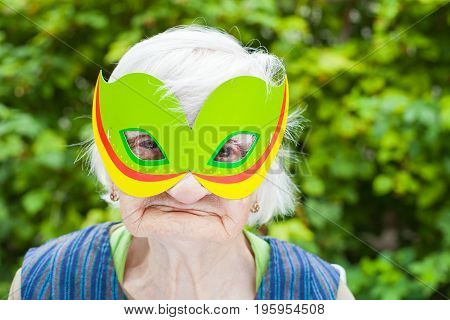 Portrait of a happy elderly woman celebrating birthday outdoor wearing a green mask