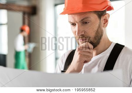 Portrait of male constructor expressing contemplation while watching at project paper indoor
