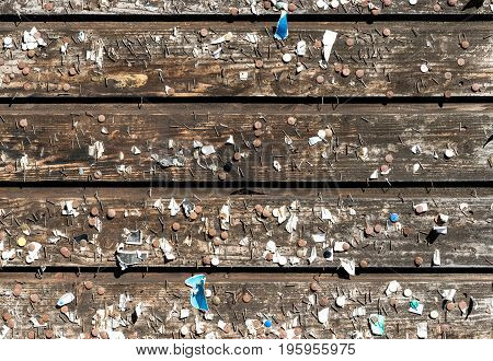 Wooden wall with old rusty pins and staples. Vintage bulletin board. Wood planks, boards are old with a beautiful rustic look.