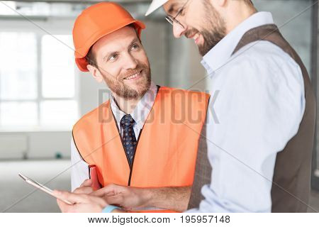 Outgoing bearded builder discussing plan of work with happy job foreman in room. He is looking at tablet