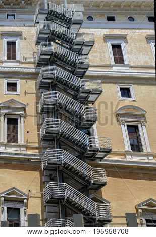Repeating pattern of a modern external staircase fire escape on an old apartment building in Rome Italy