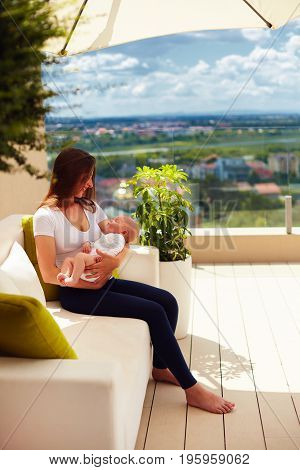 Young Mother Holding On Hands Infant Baby, While Sitting On Summer Patio Terrace