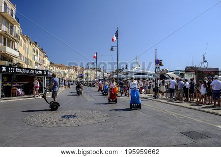 SAINT TROPEZ FRANCE - 17 JUNE 2017 - Group enjoy a guided segway tour along the streets of busy and exclusive Saint Tropez as other tourists wait to board a boat trip