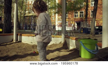 A kid playing in sandbox on a playground in a courtyard