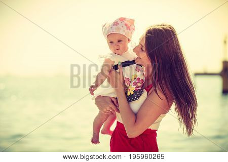 Summer family recreation concept. Mother holding and playing with little baby on beach during summertime.
