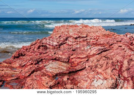 Beautiful vivid weathered rock formation with high ocean waves at the background with copy space