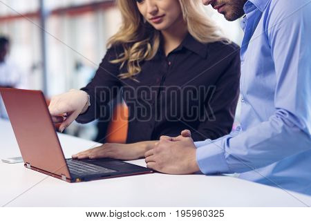 Young couple working together on a laptop in the office. Teamwork concepts