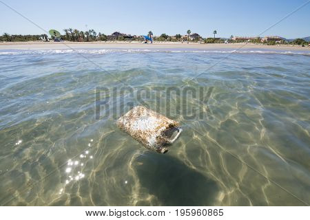 big plastic white drum bottle floating as garbage contamination in ocean water next to Beach Pine or Pinar in Grao of Castellon in Valencia Spain Europe in Mediterranean Sea