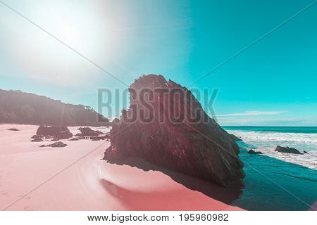 Beautiful rugged limestone rock formation on sandy ocean beach at high noon casting long shadows with sun flare and copy space