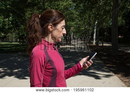 Runner Woman Using Mobile In Park Horizontal