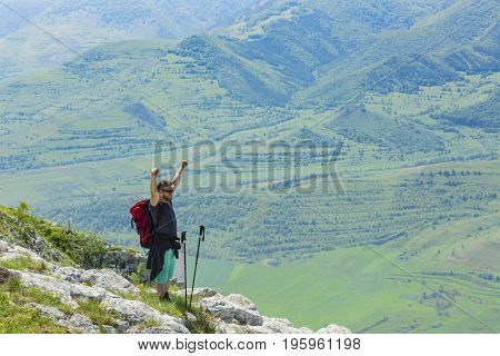 Happy hiker with hands up in the top of the mountains looking to the green valley in Apuseni Mountains in Transylvania Romania.