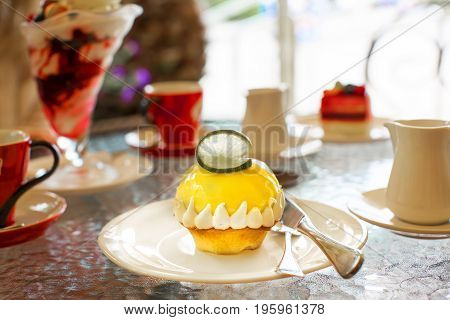 Excellent lemon cheesecake with lime slice on the table in the cafe. Against the background of other desserts and dishes