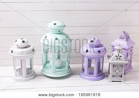 Decorative lanterns on white wooden background. Shabby chic decorations. Selective focus.