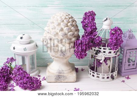 Shabby chic flowers composition. Fresh lilac flowers in box candleholders with candle decorative cone on white wooden background against turquoise wall. Selective focus.