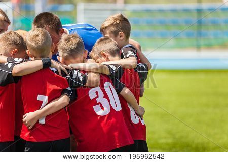 Children sports soccer team. Kids standing together on the football pitch. Soccer coach motivational team talk. Youth football soccer coach motivating players before match.