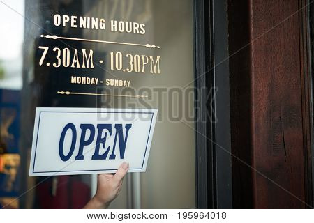Hand of shop owner with open sign