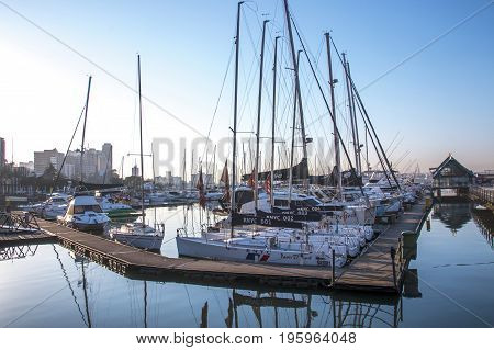 DURBAN SOUTH AFRICA - JUNE 30 2017: Early morning view of yachts moored at yacht mole in harbor against blue sky in Durban South Africa